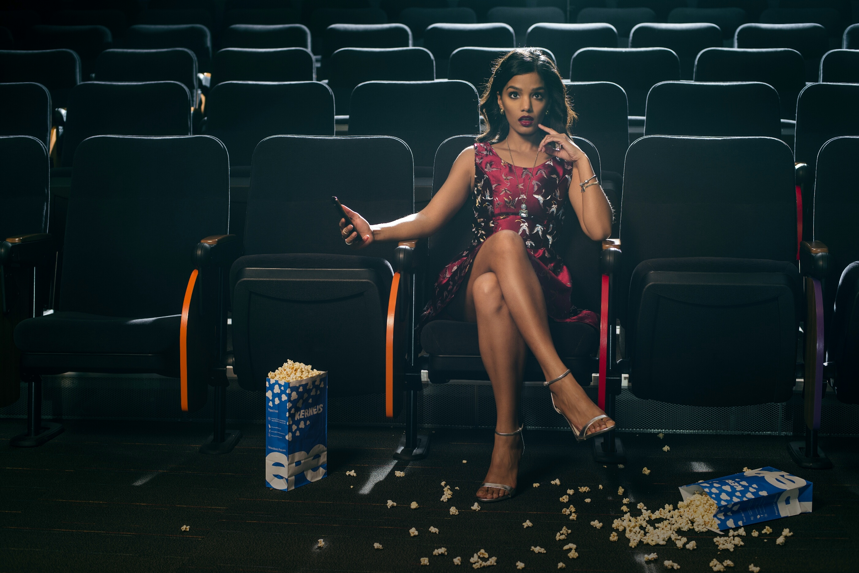 Sweet Shard sitting in a theatre with popcorn on the floor wearing her DIY red Chinese brocade dress