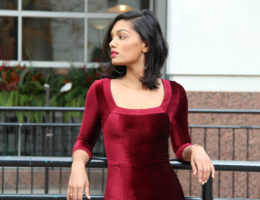 Sweet Shard DIY Red Velvet Dress High Slit. Medium Shot of Sharadha wearing dress, leaning back against a black fence
