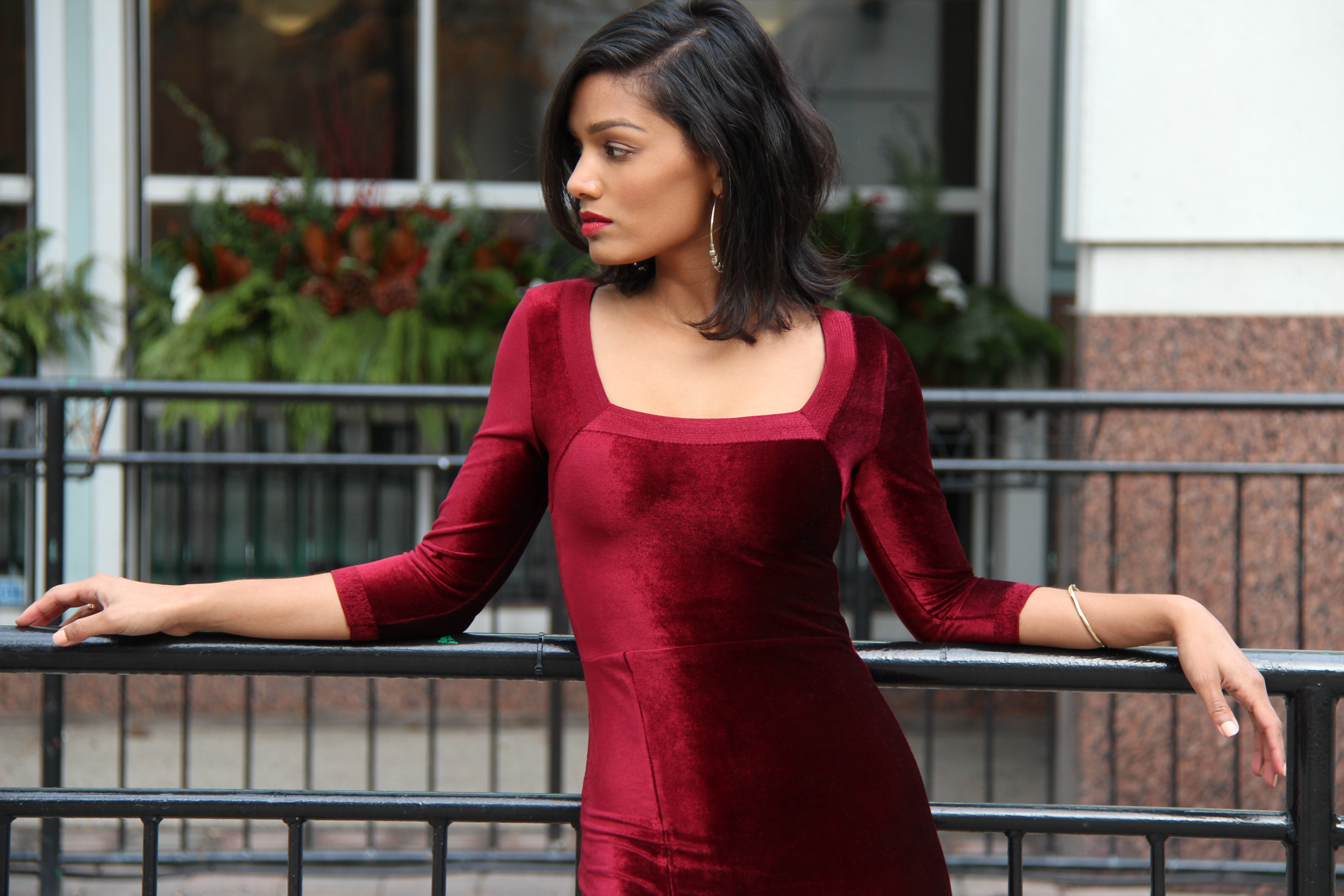 Sweet Shard DIY Red Velvet Dress High Slit. Medium Shot of Sharadha wearing dress, leaning back against a black fence